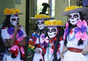 Young girls wear masks during the celebration.