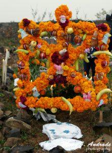 Arco decorado con ofrendas de frutas, calaveritas y animalitos de azúcar