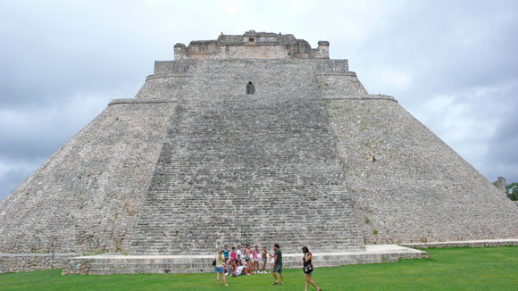Tourists explore the Temple of the Magician at Uxmal